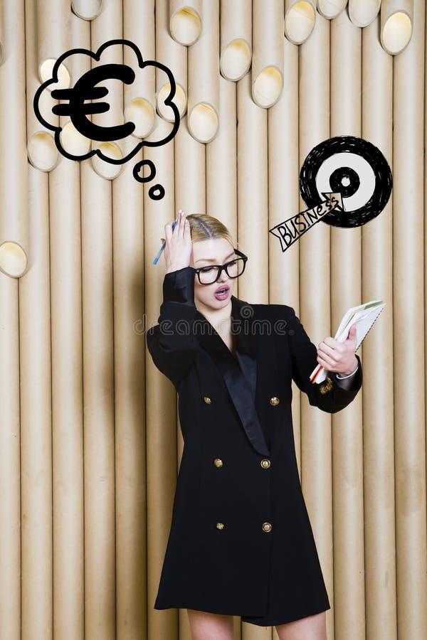 Den tänkande kvinnan som ser upp på pengar, undertecknar in bubblan och skissar målet Pengarbegrepp på designbakgrund med lampor royaltyfri bild