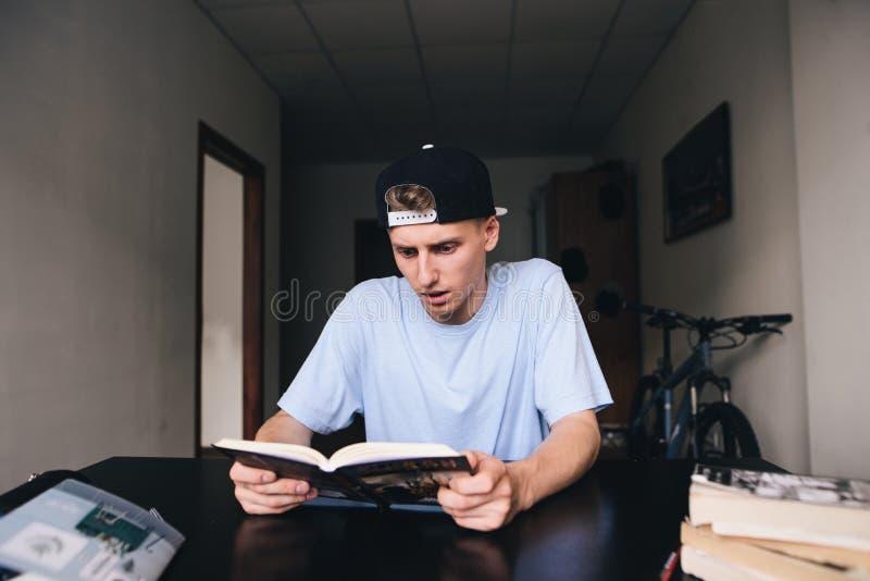 Den tänkte ut unga mannen läser en intressant bok hemma i rummet Undervisa hemma royaltyfria bilder
