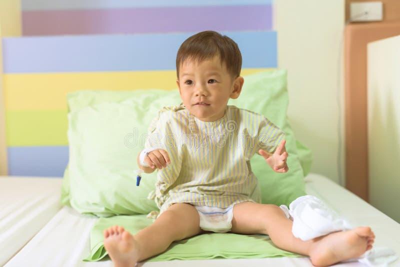 den tålmodiga pojken kopplar av på sjukhussäng royaltyfria bilder