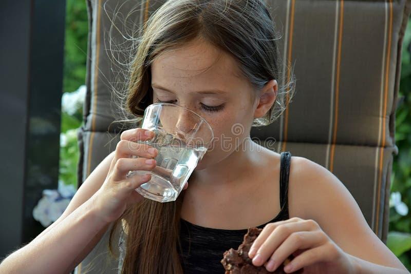 Den törstiga tonårs- flickan dricker mineralvatten arkivfoton