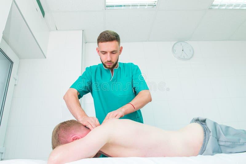 Den t?lmodiga mottagande massagen fr?n kiropraktor f?r terapeut A g?r djup silkespappermassage p? mannens skulderblad i medicinsk royaltyfri bild