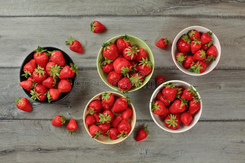 Den Tabletop sikten, små bunkar med jordgubbar, några av dem spillde på det gråa träskrivbordet arkivbilder