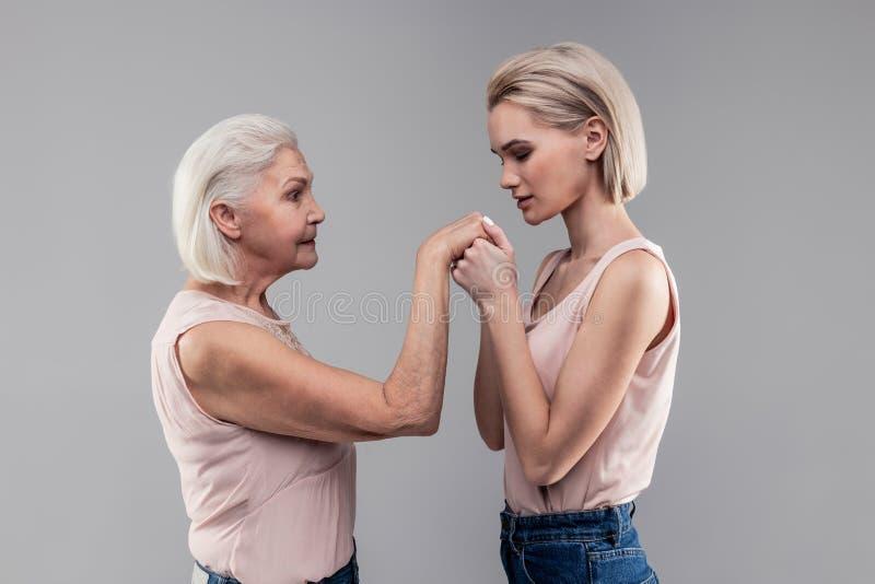 Den tacksamma blonda flickan med guppar frisyr som andas på händer av hennes höga moder arkivfoto