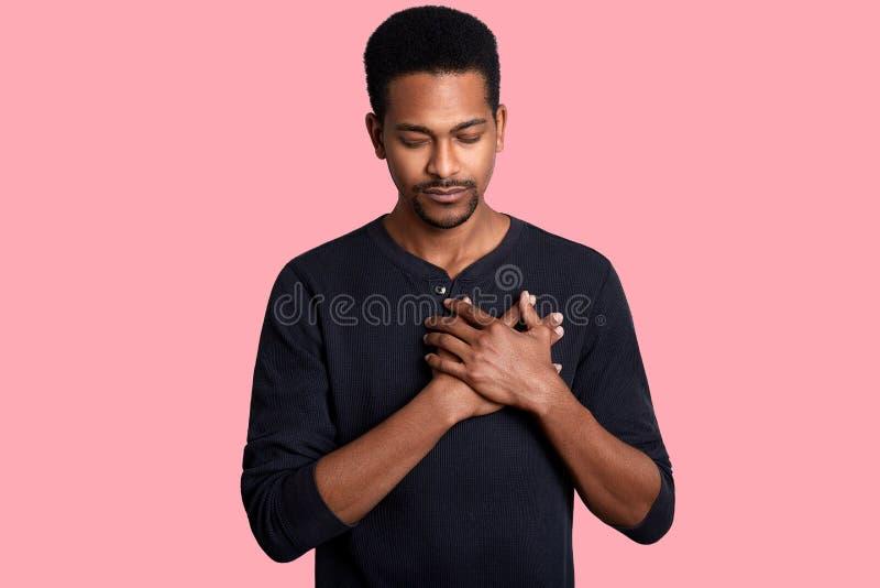 Den tacksamma lugna afrikanska mannen rymmer händer på bröstkorg, känner förälskelse, tacksamhet, ärlighet Mörkt flått grabbtack  royaltyfria bilder