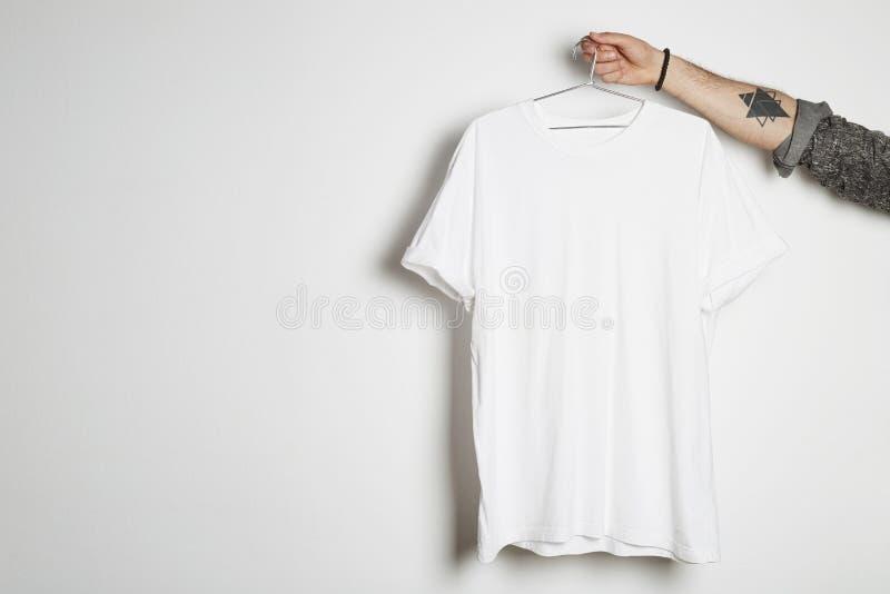 Den tatuerade hipsterhanden rymmer hängning med den tomma vita t-skjortan från högvärdig tunn bomull på vit bakgrund Modellkopia royaltyfri bild