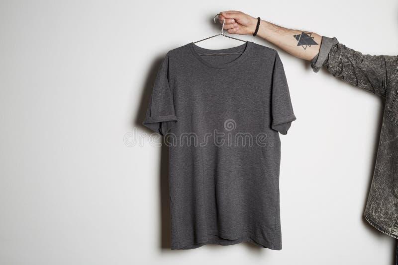 Den tatuerade manliga handen rymmer hängning med den tomma gråa t-skjortan från högvärdig tunn bomull på vit bakgrund Modellkopie arkivfoton