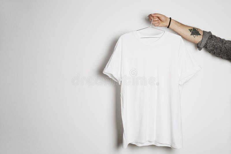 Den tatuerade manliga handen rymmer hängning med den tomma vita t-skjortan från högvärdig tunn bomull på vit bakgrund Modellkopie royaltyfri fotografi