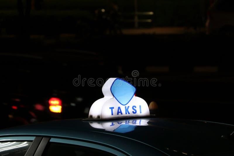 Den taxiljustecknet eller taxin undertecknar i bl? och vit f?rg p? biltaket p? gatan i den m?rka natten royaltyfri fotografi