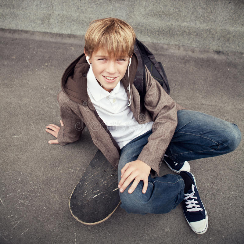 Den teen skolan sitter på skateboarden nära skola royaltyfria bilder