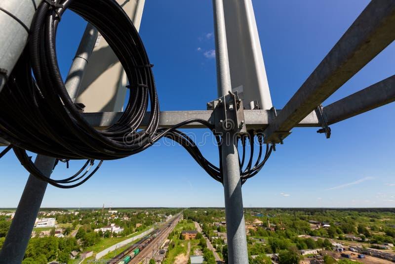 Den telekommunikationtornet eller masten med mikrov?gen, radios?nder panelantenner, utomhus- avl?gsna radioenheter, maktkablar so arkivbild