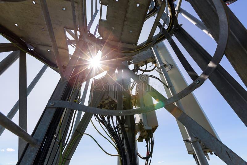 Den telekommunikationtornet eller masten med mikrov?gen, radios?nder panelantenner, utomhus- avl?gsna radioenheter, maktkablar so arkivbilder
