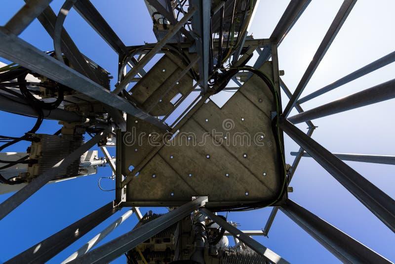 Den telekommunikationtornet eller masten med mikrov?gen, radios?nder panelantenner, utomhus- avl?gsna radioenheter, maktkablar so royaltyfria foton