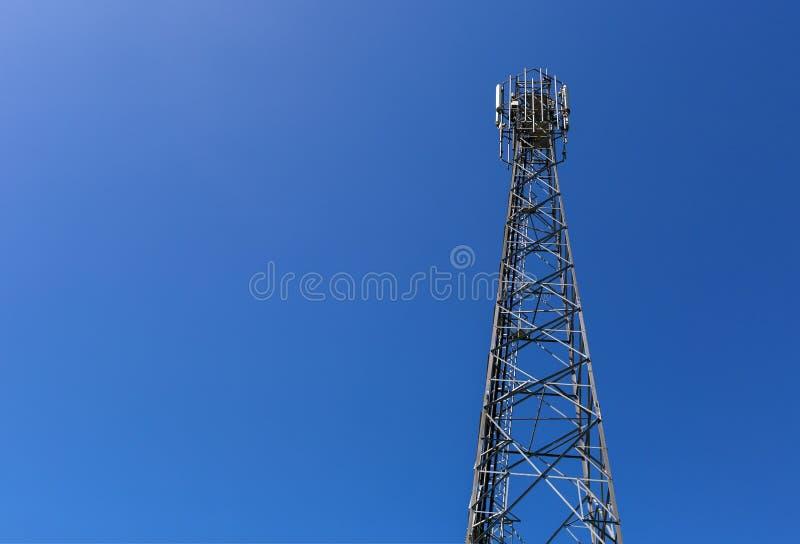 Den telekommunikationtornet eller masten med mikrov?gen, radios?nder panelantenner, utomhus- avl?gsna radioenheter, maktkablar so arkivfoton