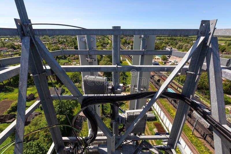 Den telekommunikationtornet eller masten med mikrov?gen, radios?nder panelantenner, utomhus- avl?gsna radioenheter, maktkablar so royaltyfri bild