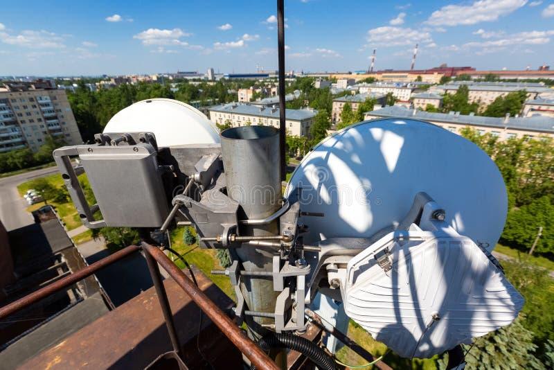 Den telekommunikationtornet eller masten med mikrov?gen, radios?nder panelantenner, utomhus- avl?gsna radioenheter, maktkablar so royaltyfria bilder