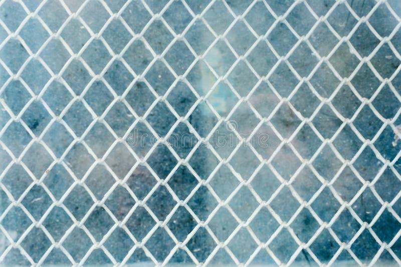 Den texturerade bakgrunden av ett vävt grunt ingrepp bak ett blinkande exponeringsglas Blått smutsar ner exponeringsglas Tappning royaltyfri foto