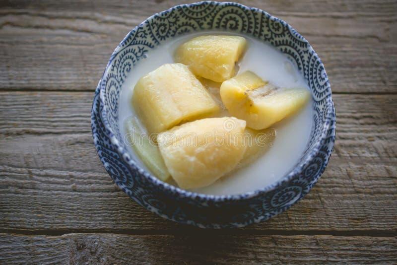 Den thailändska bananen i kokosnöt mjölkar med morgonljus på träbackgro royaltyfria foton