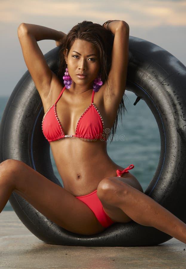 Den thailändska bikinin modellerar med röret royaltyfri foto