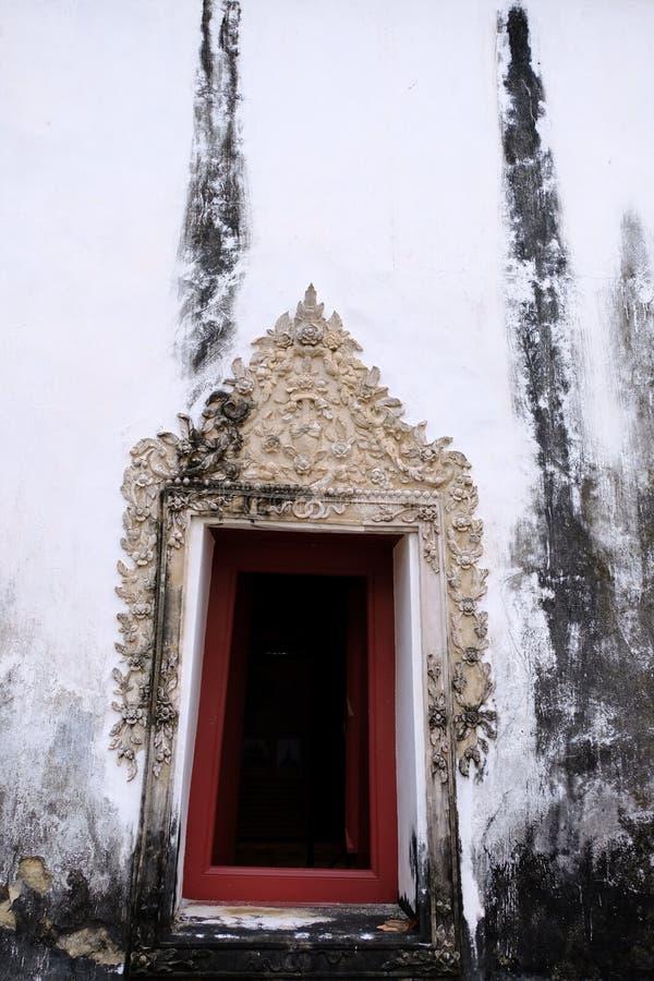 Den thailändska konststuckaturen av fönsterramen med vit färg och den röda träfärgramen royaltyfria foton