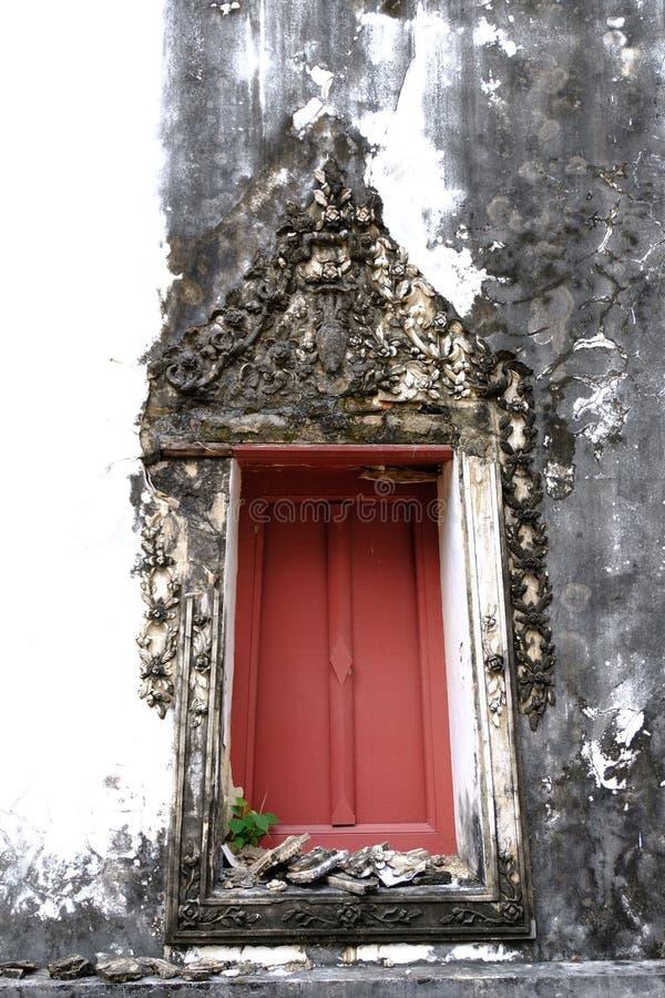 Den thailändska konststuckaturen av den forntida fönsterramen med rött trä med den blom- vinrankamodellen för stuckatur royaltyfri fotografi