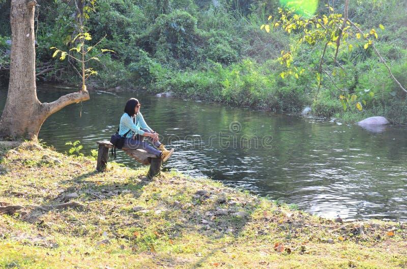 Den thailändska kvinnaståenden sitter på bänk på skogen i Suan Phueng arkivbild