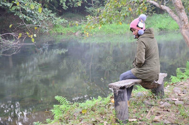 Den thailändska kvinnaståenden sitter på bänk på skogen i Suan Phueng royaltyfria foton