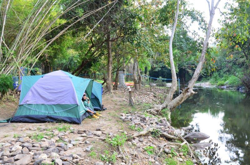 Den thailändska kvinnaståenden sitter på tältlägret i Suan Phueng fotografering för bildbyråer