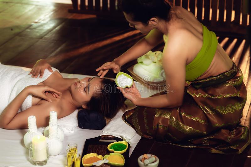 Den thailändska massagen för brunnsorten för flickaterapeutkroppen och liggande avkoppling i affärsatt massera och salong shoppar arkivfoto