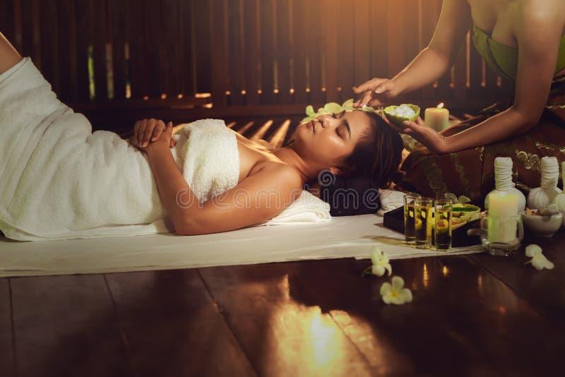 Den thailändska massagen för brunnsorten för flickaterapeutkroppen och liggande avkoppling i affärsatt massera och salong shoppar royaltyfri foto