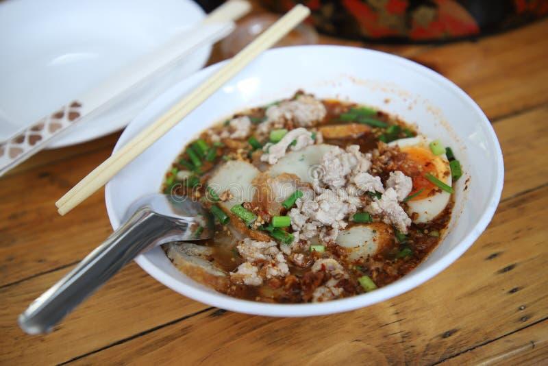 Den thailändska stilfläskkotlettnudeln har det kokade ägget in arkivbild