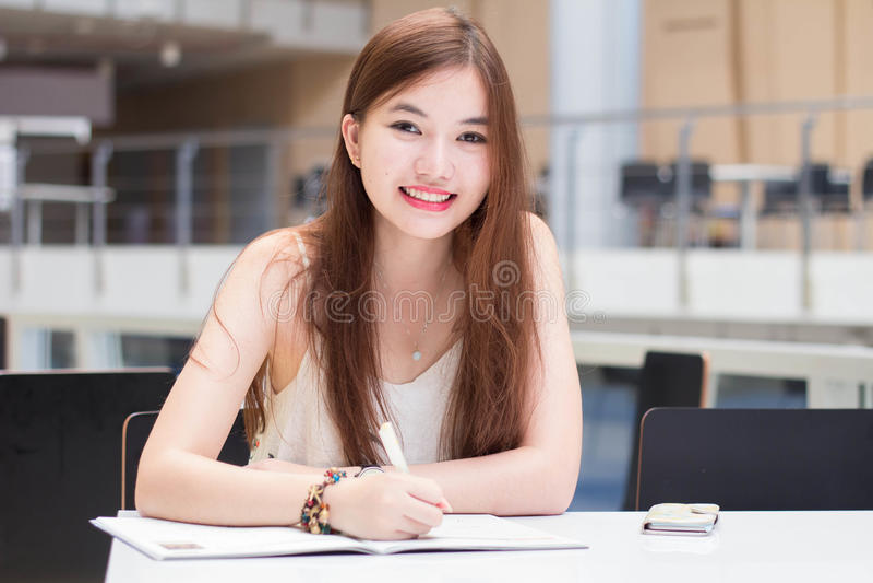 Den thailändska vuxna härliga flickan skriver en bok och ett leende i universitet royaltyfri bild