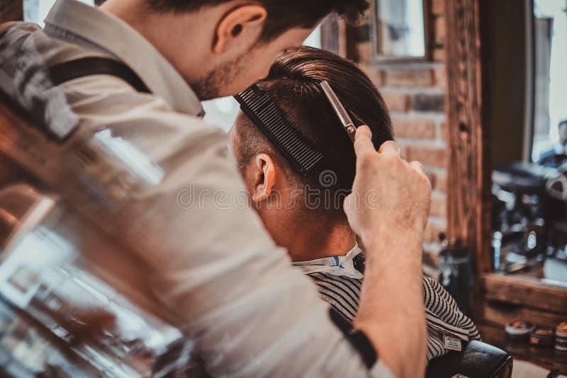 Den Thendy frisören på den moderna frisersalongen arbetar på klientens frisyr royaltyfri bild