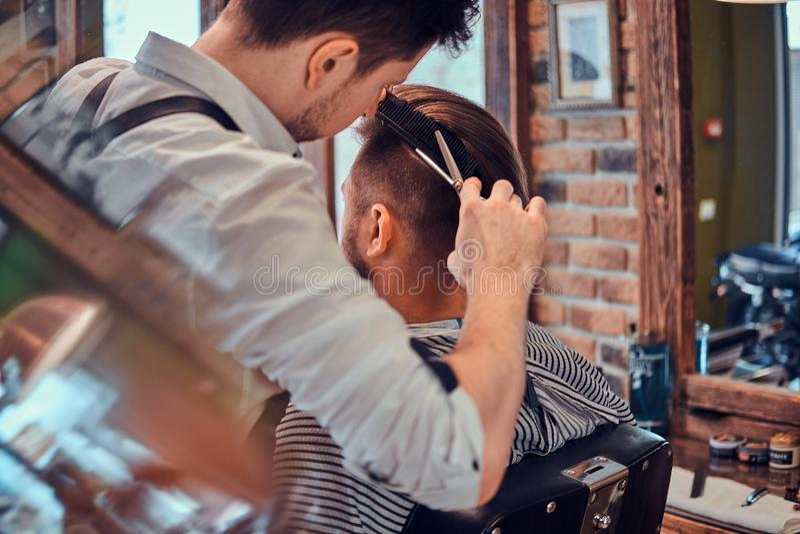 Den Thendy frisören på den moderna frisersalongen arbetar på klientens frisyr royaltyfri fotografi