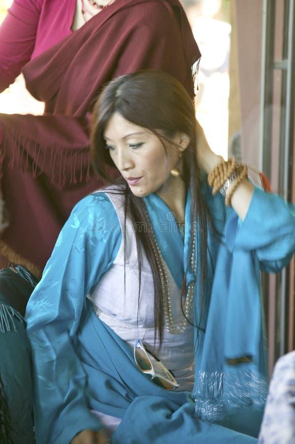 Den tibetana kvinnan i traditionell klänning deltar i buddistisk ceremoni för Amitabha bemyndigande, meditationmontering i Ojai,  royaltyfri bild