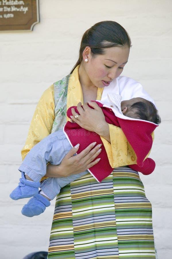Den tibetana kvinnan i traditionell klänning rymmer barnet under buddistisk ceremoni för Amitabha bemyndigande, meditationmonteri royaltyfri foto