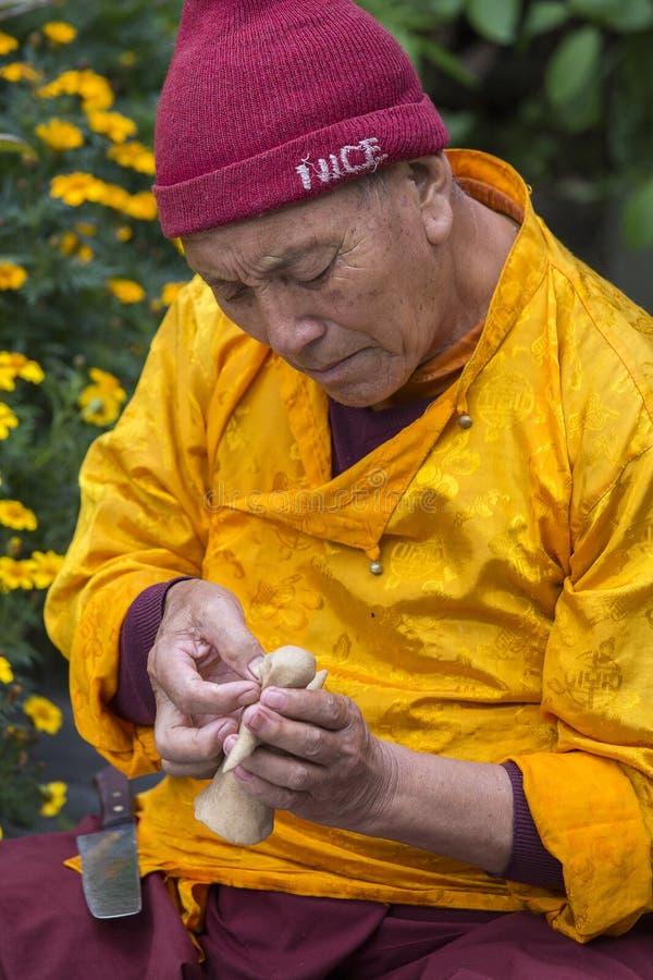 Den tibetana munken högg diagramet av tsampaen för gudkornmjöl för buddistisk religiös ceremoni i Himalayas byn, Nepal Slut u arkivfoton