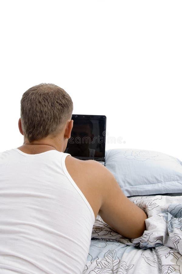 den tillbaka bärbar dator som lägger mannen, poserar arkivbild