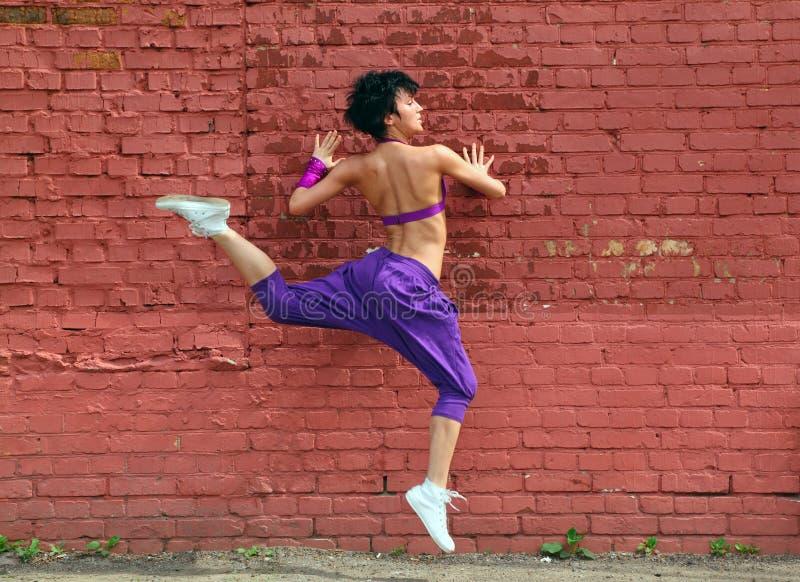 den tillbaka flickan hoppar att lyfta för ben arkivfoto
