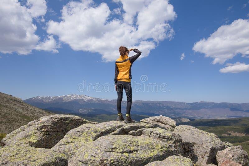 Den tillbaka kvinnan som ser in i avstånd från, vaggar överkanten av berget arkivbilder
