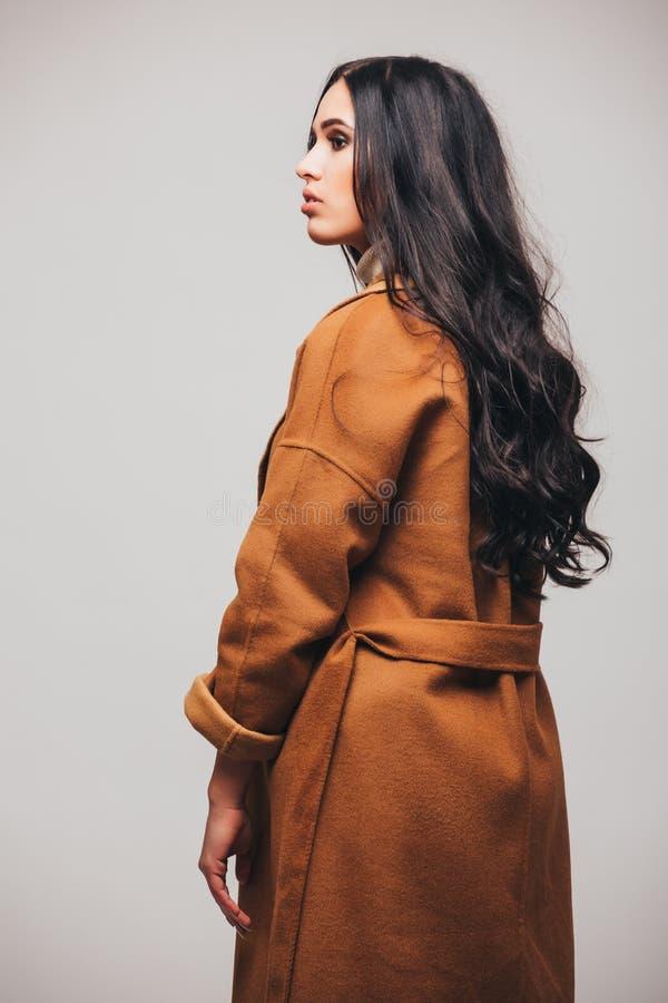 Den tillbaka sidan av modestudiofotoet av den ursnygga sinnliga kvinnan med mörkt rakt hår bär det eleganta bruna laget arkivfoton
