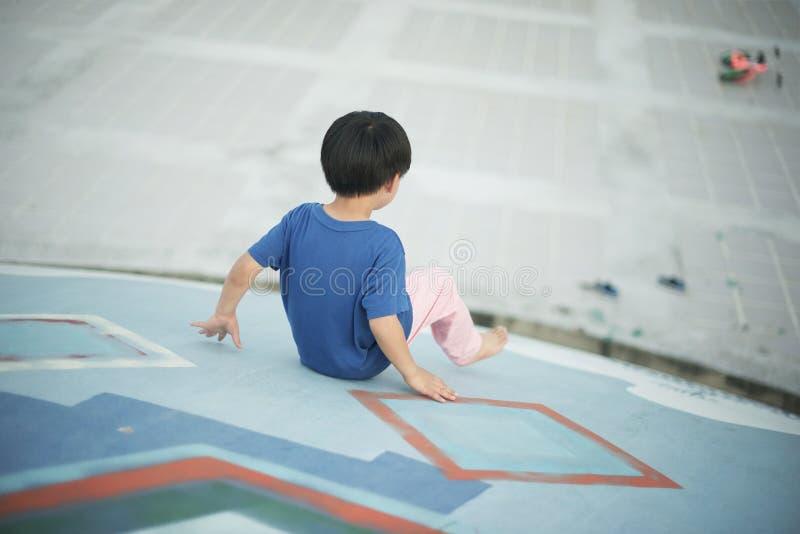 Den tillbaka sidan av pojken som ner går, parkerar glidbanan arkivbilder