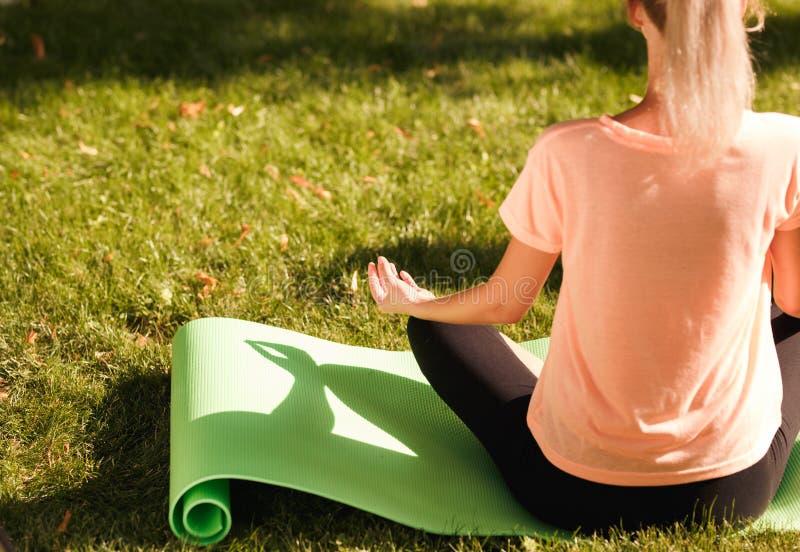 Den tillbaka sikten av övande yoga för kvinnan sitter i lotusblommaposition sund livsstil för begrepp fotografering för bildbyråer