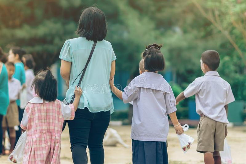 Den tillbaka sikten av den asiatiska modern leder hennes dotter och son till skola royaltyfri bild
