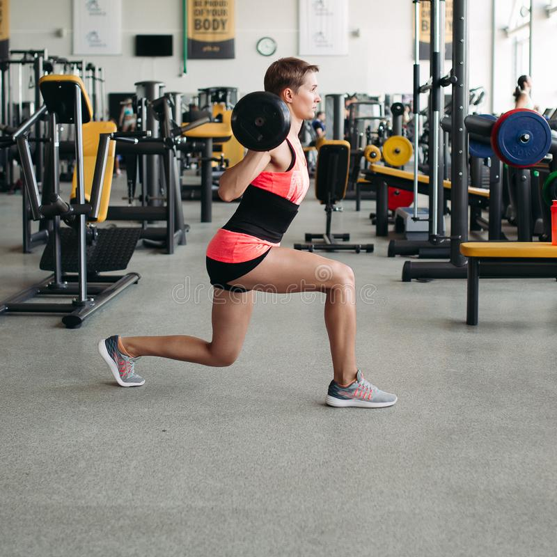 Den tillbaka sikten av brunettkvinnan, i rosa sportar bär att göra genomkörare med skivstången arkivbild