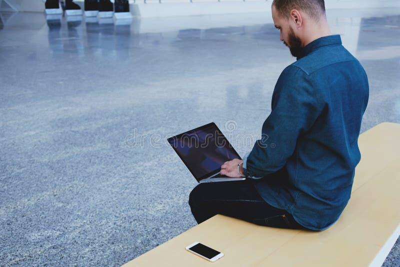 Den tillbaka sikten av Caucasian mankeyboarding på bärbar datordatoren med den tomma kopieringsutrymmeskärmen för ditt textmeddel arkivbild