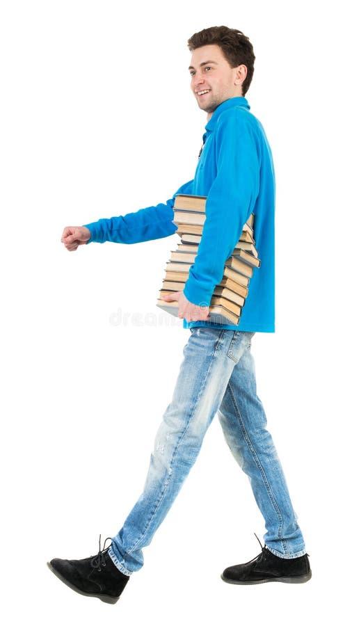 Den tillbaka sikten av den gående stiliga mannen bär en bunt av böcker royaltyfri bild