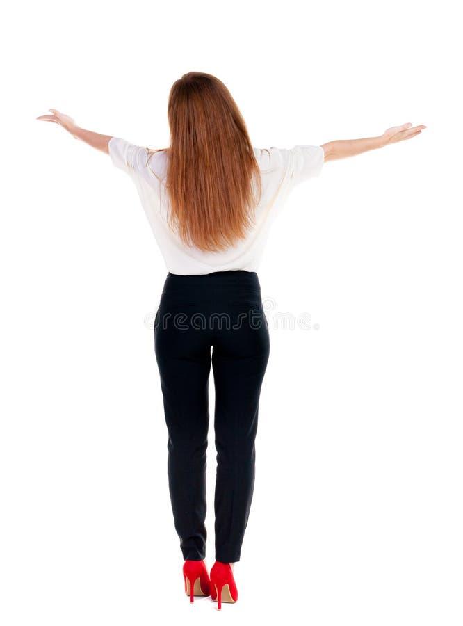 Den tillbaka sikten av den härliga affärskvinnan i följet som ser väggen och håll, räcker upp fotografering för bildbyråer