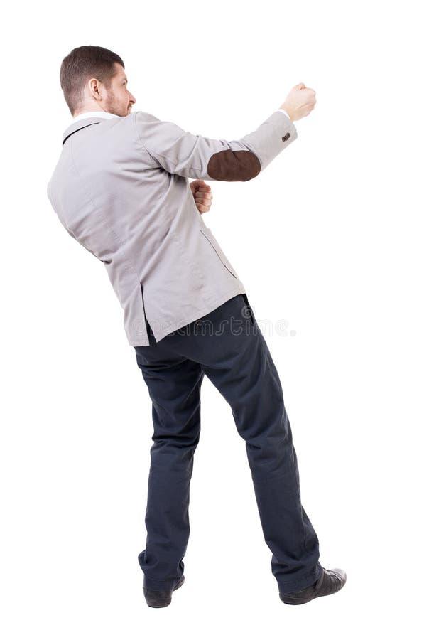 Den tillbaka sikten av den stående mannen som uppifrån drar ett rep eller, håller fast vid t arkivfoto