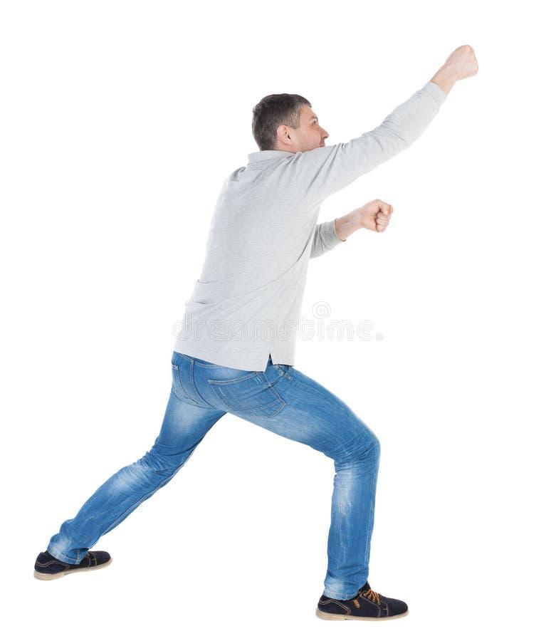 Den tillbaka sikten av den stående mannen som uppifrån drar ett rep eller, håller fast vid t arkivfoton