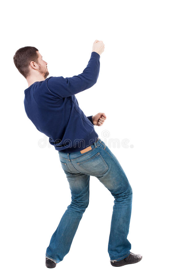 Den tillbaka sikten av den stående mannen som uppifrån drar ett rep eller, håller fast vid t royaltyfria bilder
